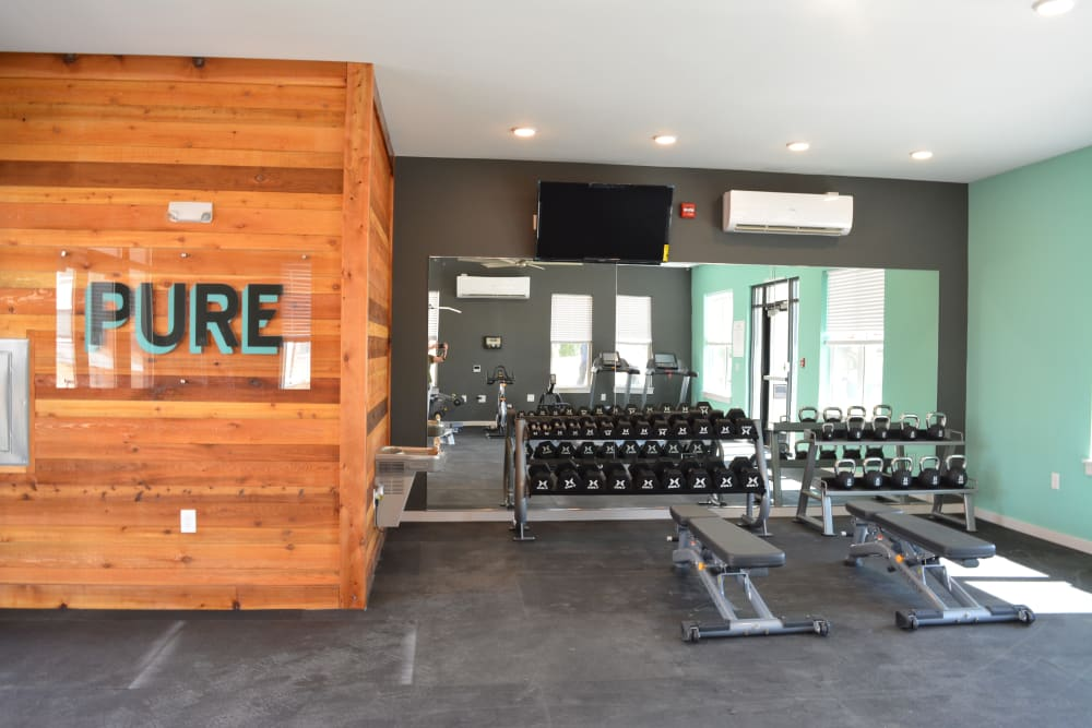 A fitness center with a mirror-walled for weight lifting at Pure St. Peters in Saint Peters, Missouri