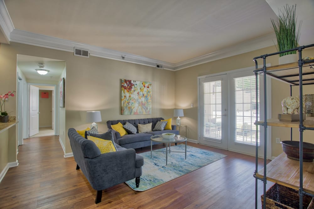 Living room with double doors to outdoor patio at Atkins Circle Apartments & Townhomes in Charlotte, North Carolina