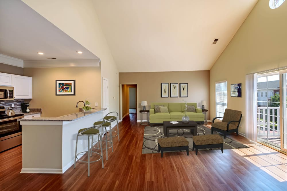 Living room and kitchen with breakfast bar for more seating at Christopher Wren Apartments & Townhomes in Wexford, Pennsylvania