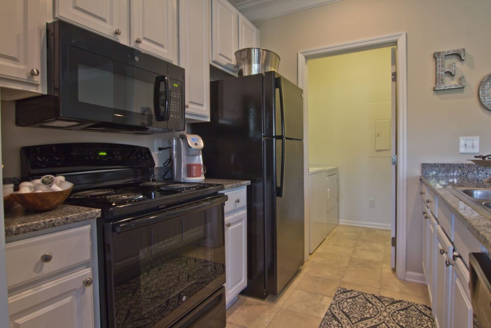 Kitchen with white cabinets and black appliances at Easton Commons Apartments & Townhomes in Columbus, Ohio