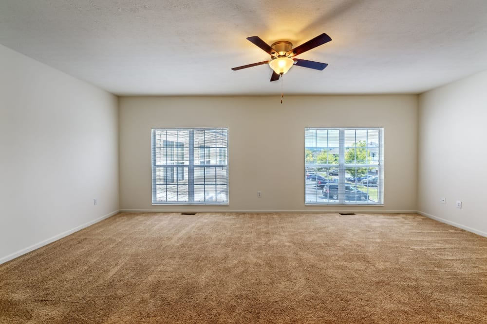 Open bedroom with carpeted floors and ceiling fan at The Waterfront Apartments & Townhomes in Munhall, Pennsylvania