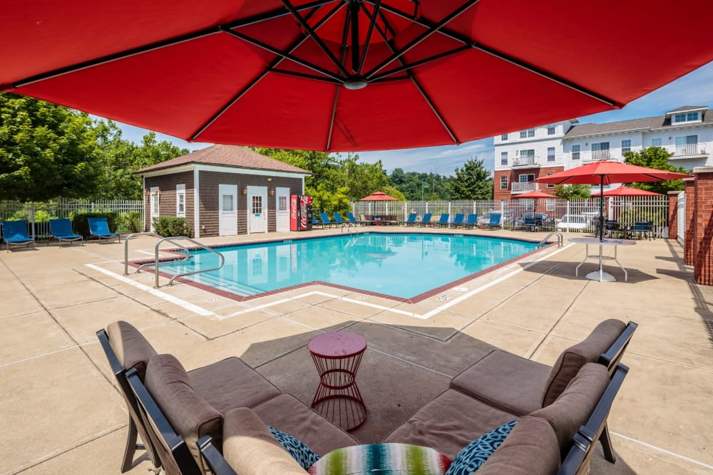 Poolside seating under umbrella next to swimming pool at The Waterfront Apartments & Townhomes in Munhall, Pennsylvania