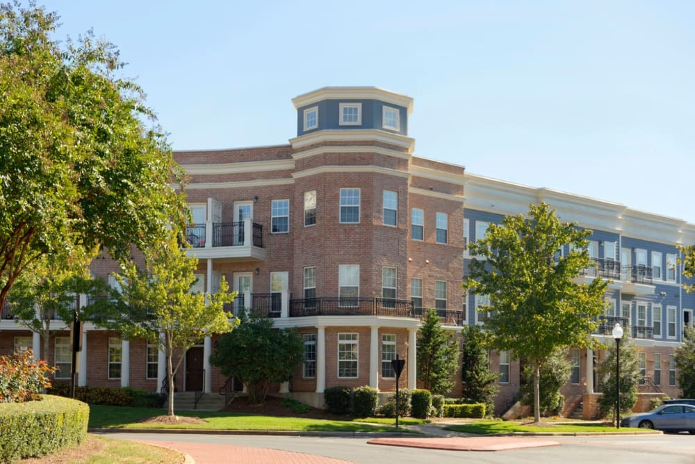 Beautiful brick building surrounded by trees and grass at Worthington Apartments & Townhomes in Charlotte, North Carolina
