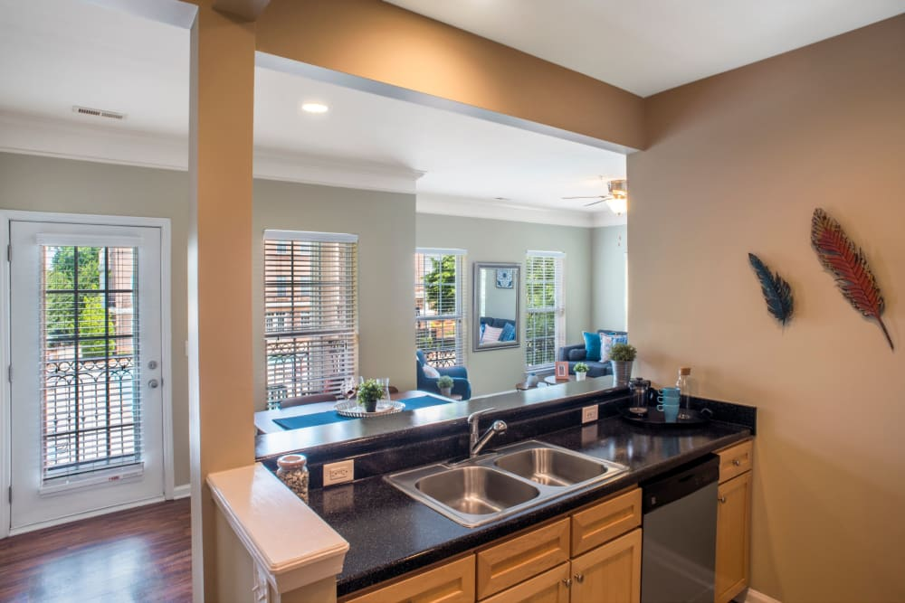 Kitchen sing with breakfast bar behind at Worthington Apartments & Townhomes in Charlotte, North Carolina