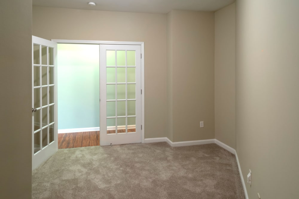 Carpeted room with double glass doors at Worthington Apartments & Townhomes in Charlotte, North Carolina