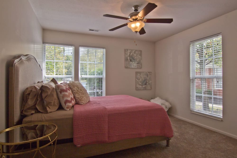 Bedroom with ceiling fan and large windows at The Woods at Polaris Parkway Apartments & Townhomes in Westerville, Ohio