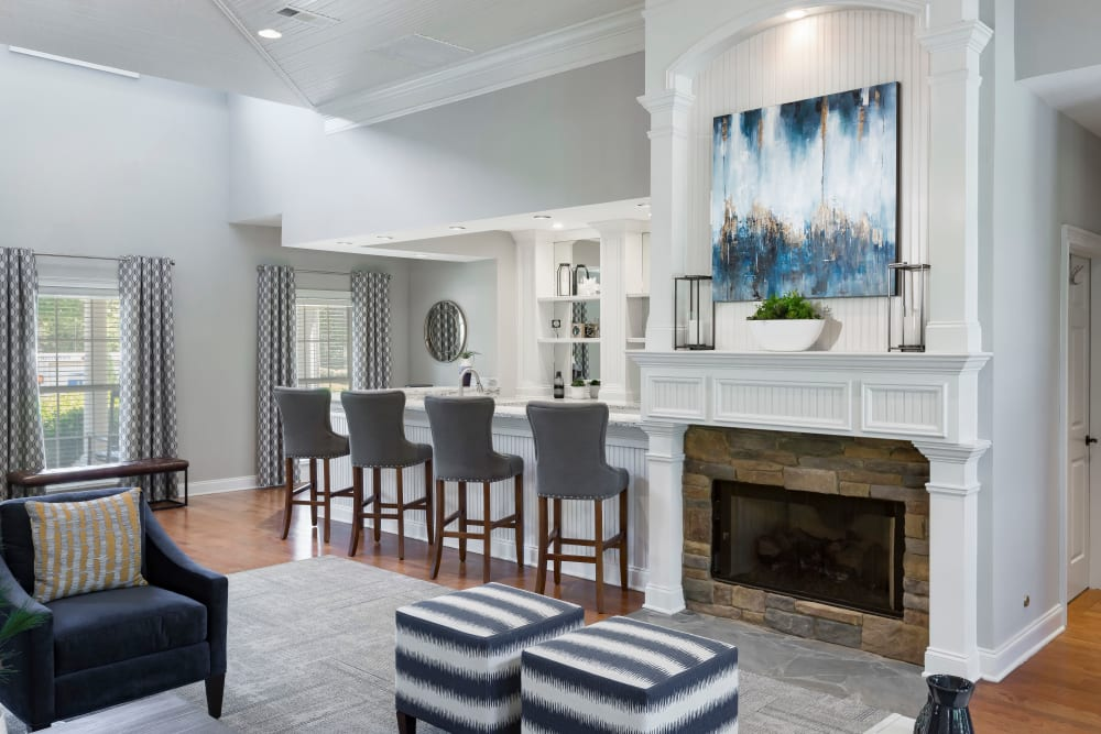 Resident clubhouse lounge with a fireplace and bar seating at The Vinings at Newnan Lakes in Newnan, Georgia