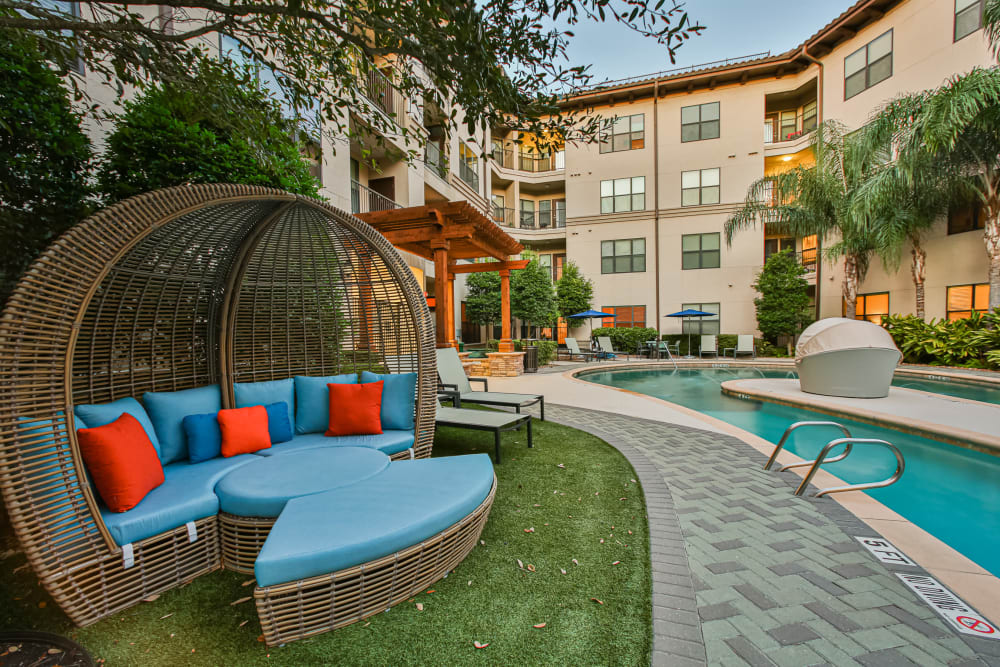 Covered outdoor couches by pool at Broadstone Toscano in Houston, Texas