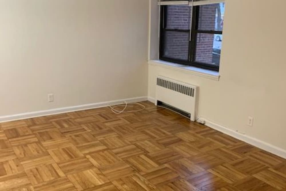 Living room with wood style flooring and a heater at King Alfred Apartments in Passaic, New Jersey