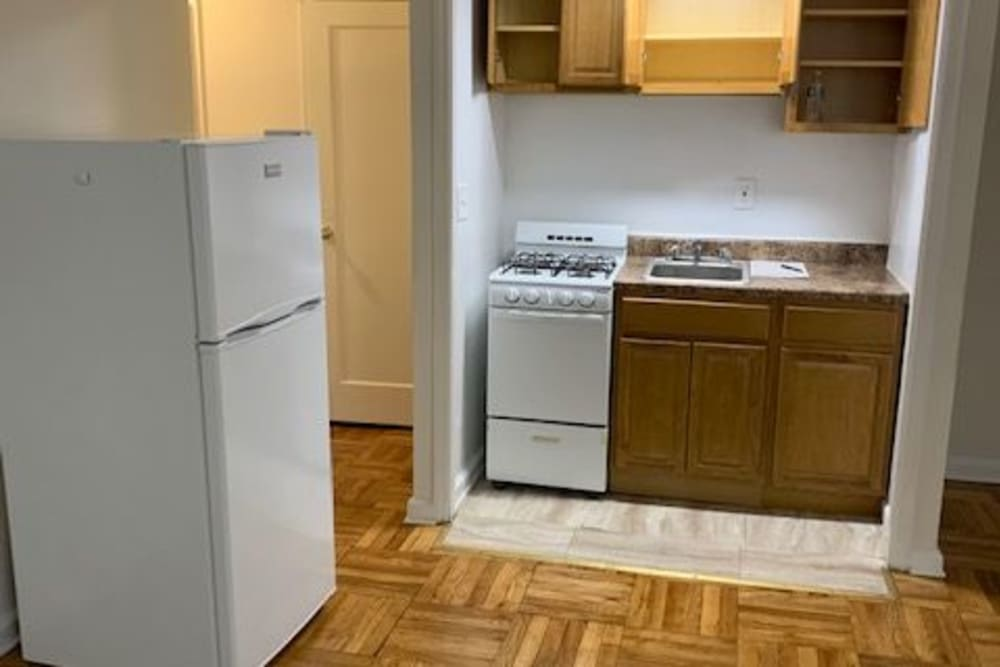 Empty kitchen area with wood style floors at King Alfred Apartments in Passaic, New Jersey