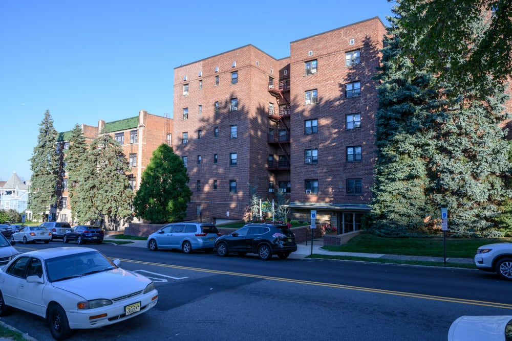 Exterior with large trees shading the building at King Alfred Apartments in Passaic, New Jersey