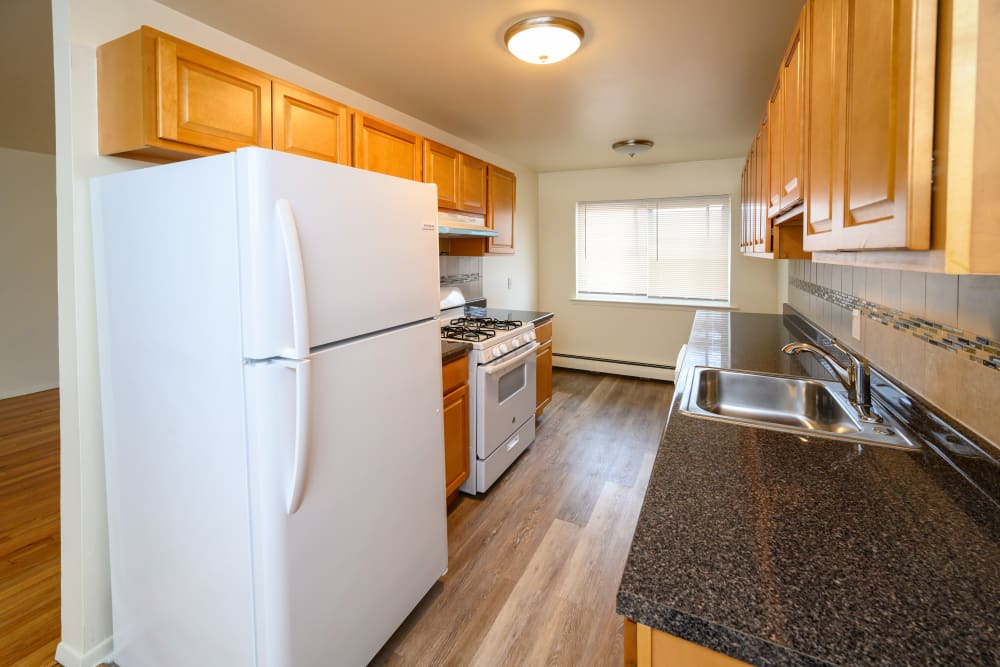 Black countertops in kitchen with clean white fridge at Rutgers Court Apartments in Belleville, New Jersey