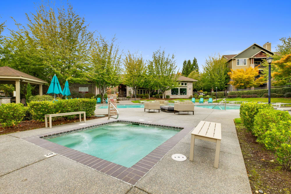 Beautiful resort-style swimming pool with lounge chairs at The Grove at Orenco Station in Hillsboro, Oregon
