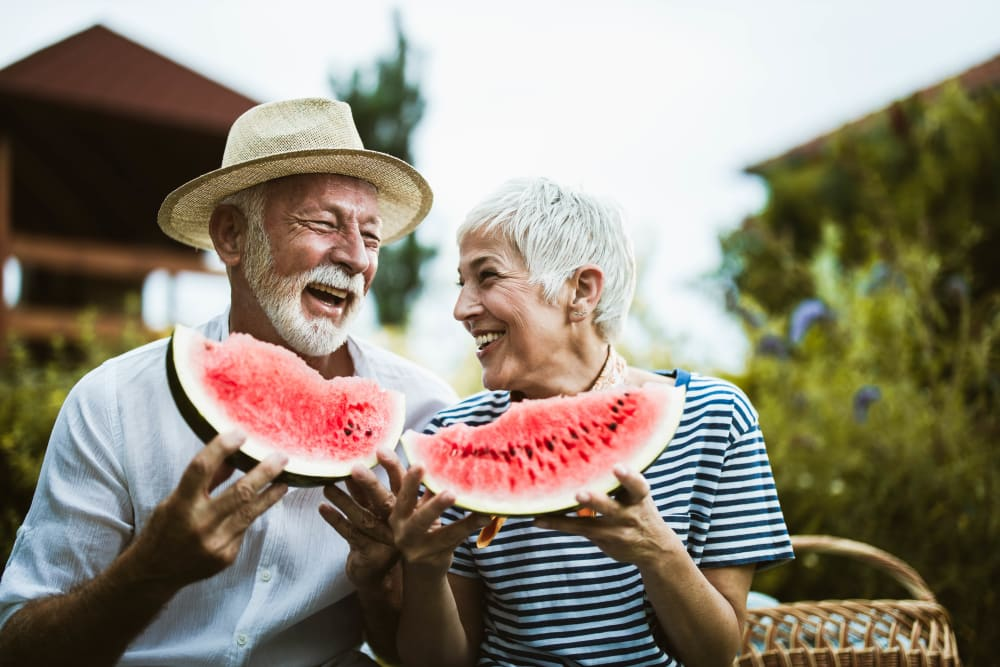Happy couple enjoying watermelon in Baltimore, Maryland near Alcott Place
