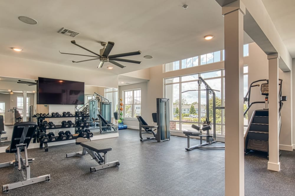 A fitness center with a couple large-screen TVs at Marina Villa in Norfolk, Virginia