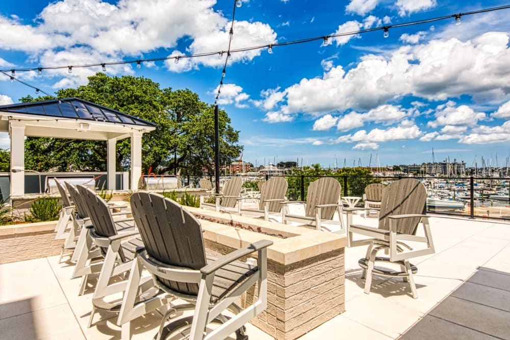 A sundeck with a firepit and comfortable chairs at Marina Villa in Norfolk, Virginia