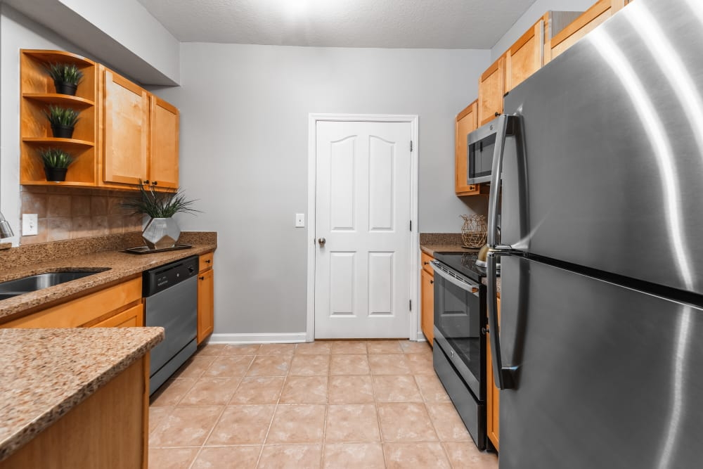 Kitchen with stainless steal appliances and wooden cabinets at Eddison at Deerwood Park in Jacksonville, Florida