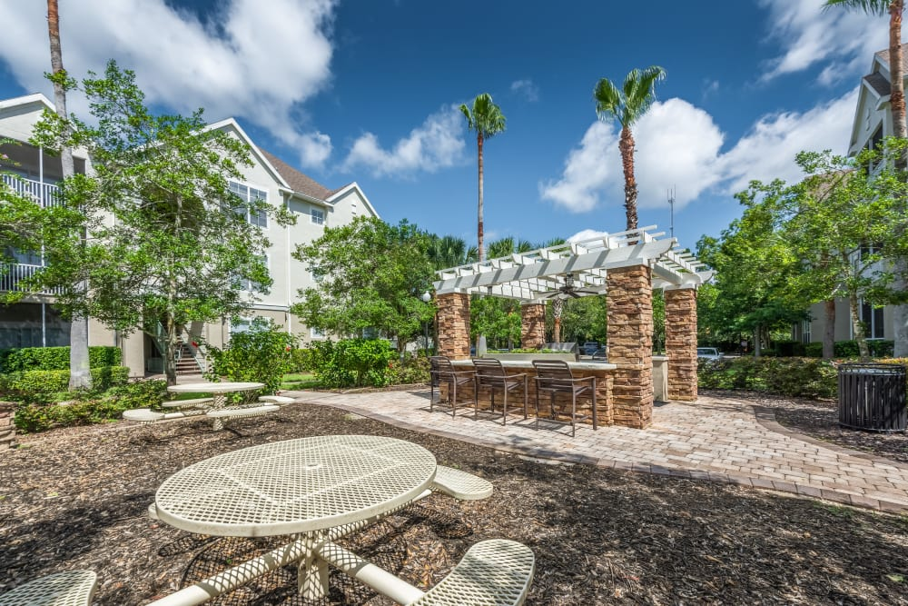 Big outdoor grilling area with tables at Eddison at Deerwood Park in Jacksonville, Florida