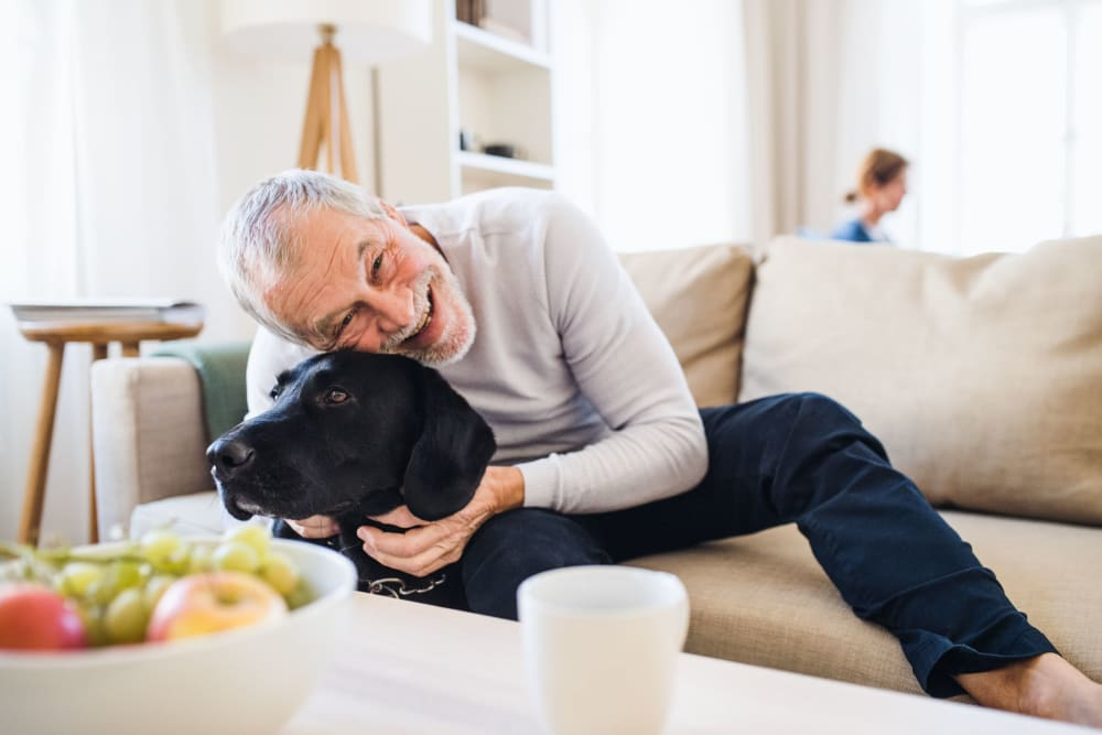 Man snuggling with his dog in his living room at Fairview Senior Apartments in Rising Sun, Maryland