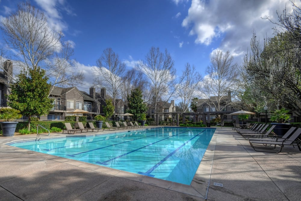 A poolside sundeck with plenty of lounge chairs at Larkspur Woods in Sacramento, California