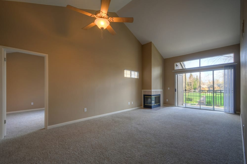 A living room with plush carpeting and a ceiling fan at Larkspur Woods in Sacramento, California