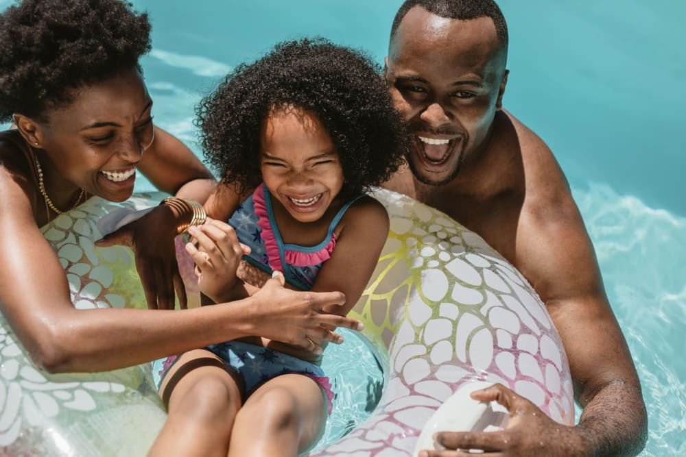 Family enjoying a beautiful day in the swimming pool at Park at Winterset Apartments in Owings Mills, Maryland