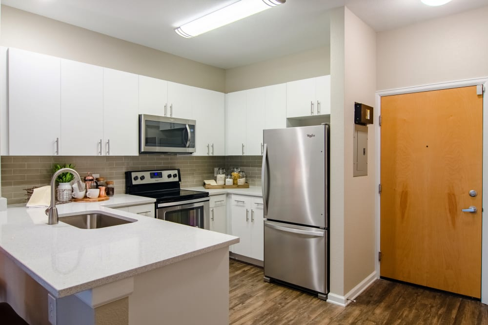 Bright kitchen with wood-style flooring at Summit at Flatirons Apartments in Broomfield, Colorado