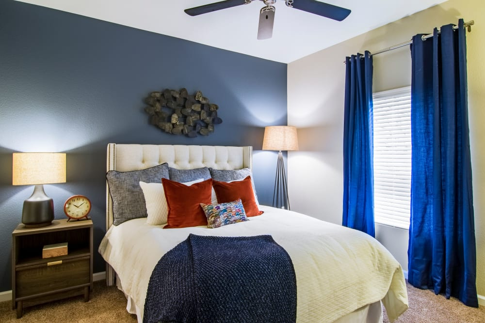 Cozy bedroom with a ceiling fan at Summit at Flatirons Apartments in Broomfield, Colorado