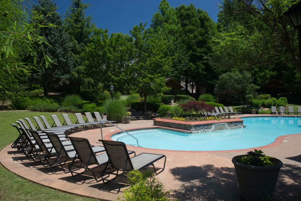 Chaise lounge chairs and mature trees around the pool area at The Vinings at Newnan Lakes in Newnan, Georgia