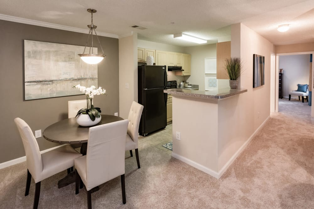Dining nook with an accent wall next to a model home's kitchen at The Vinings at Newnan Lakes in Newnan, Georgia