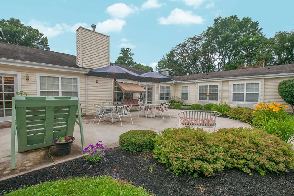 Back patio with landscaped yard and seating with umbrella at Randall Residence of Newark in Newark, Ohio