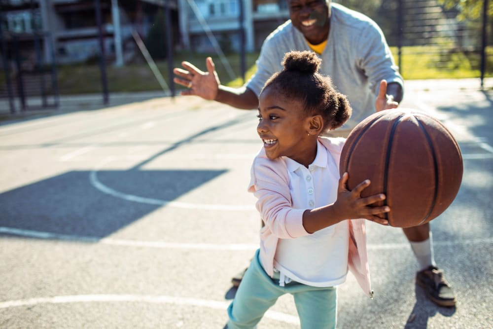 Resident and their kid playing basketball together at Autumn Ridge in Waukee, Iowa