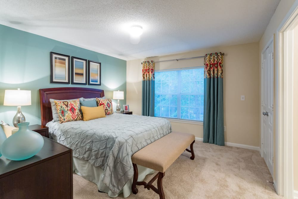Model home's primary bedroom with an accent wall and draped bay windows at The Vinings at Newnan Lakes in Newnan, Georgia
