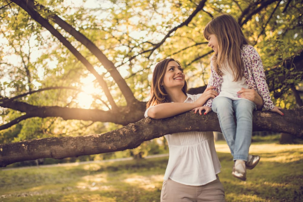 Mother with daughter as she enjoys herself climbing a tree near The Park at Ashford in Arlington, Texas