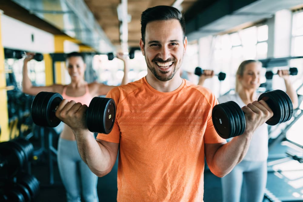 Man at fitness center working out with a smile on his face at Trails of Towne Lake in Irving, Texas
