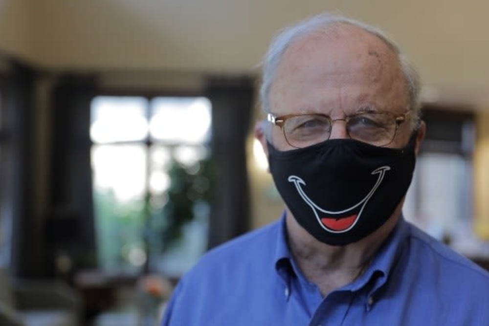 Resident wearing a mask with a smile on it at The Heritage at Creek Valley in Carrolton, Texas