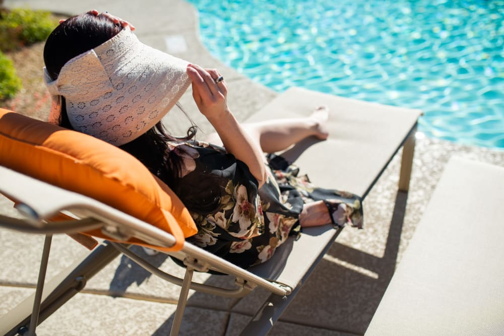 Woman lounging by the resort style swimming pool at ArLo in Phoenix, Arizona