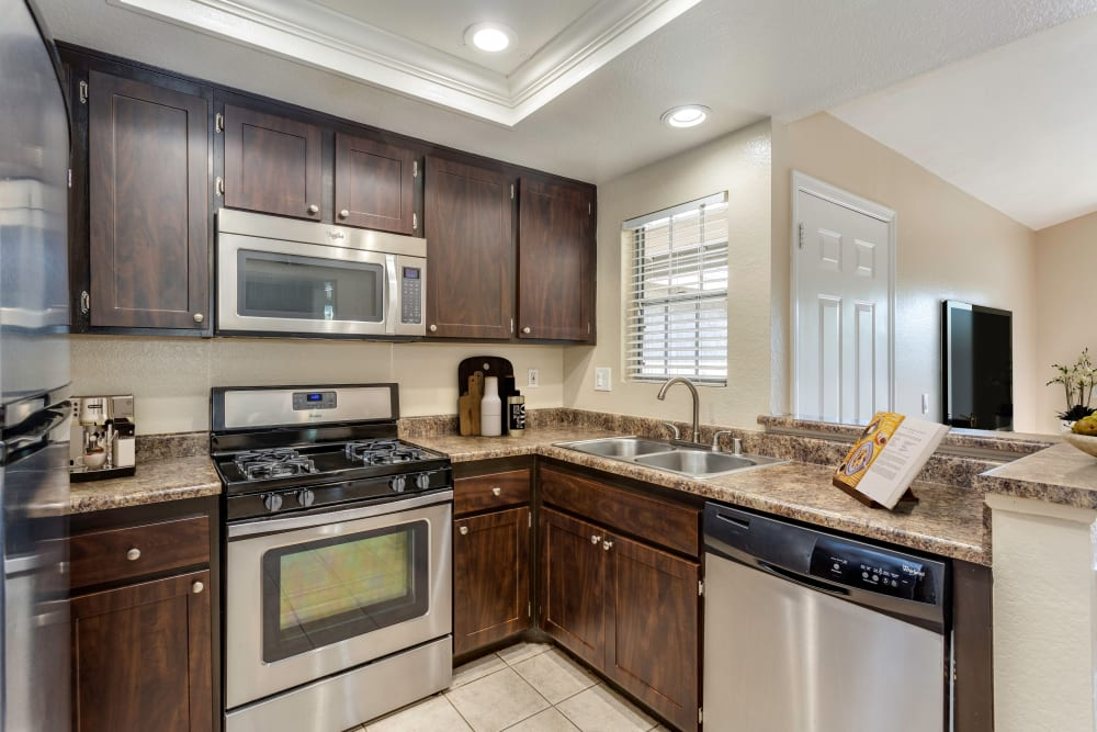 A renovated kitchen with espresso cabinetry and ceramic tile at Village Oaks in Chino Hills, California