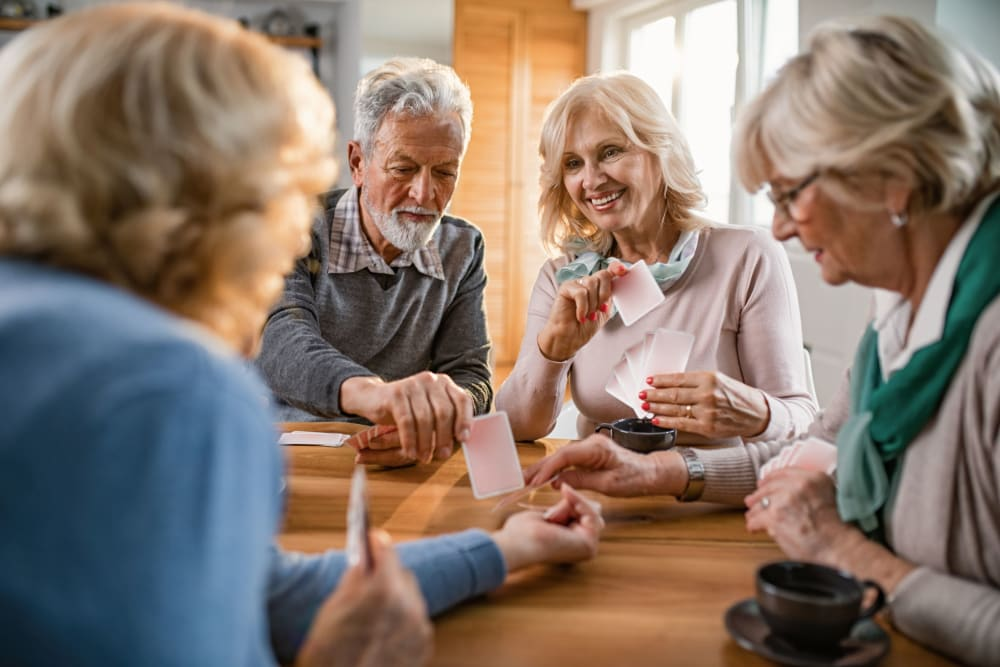Friends playing cards at Winding Commons Senior Living in Carmichael, California