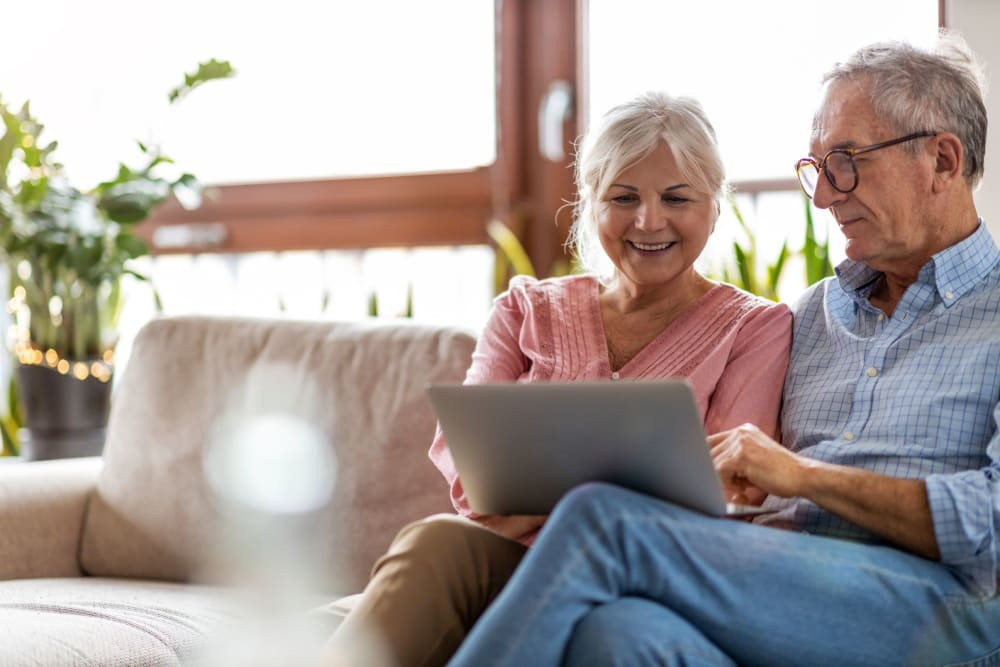 Couple looking at their laptop together at Castle Vista Senior Duplex Community in Atwater, California