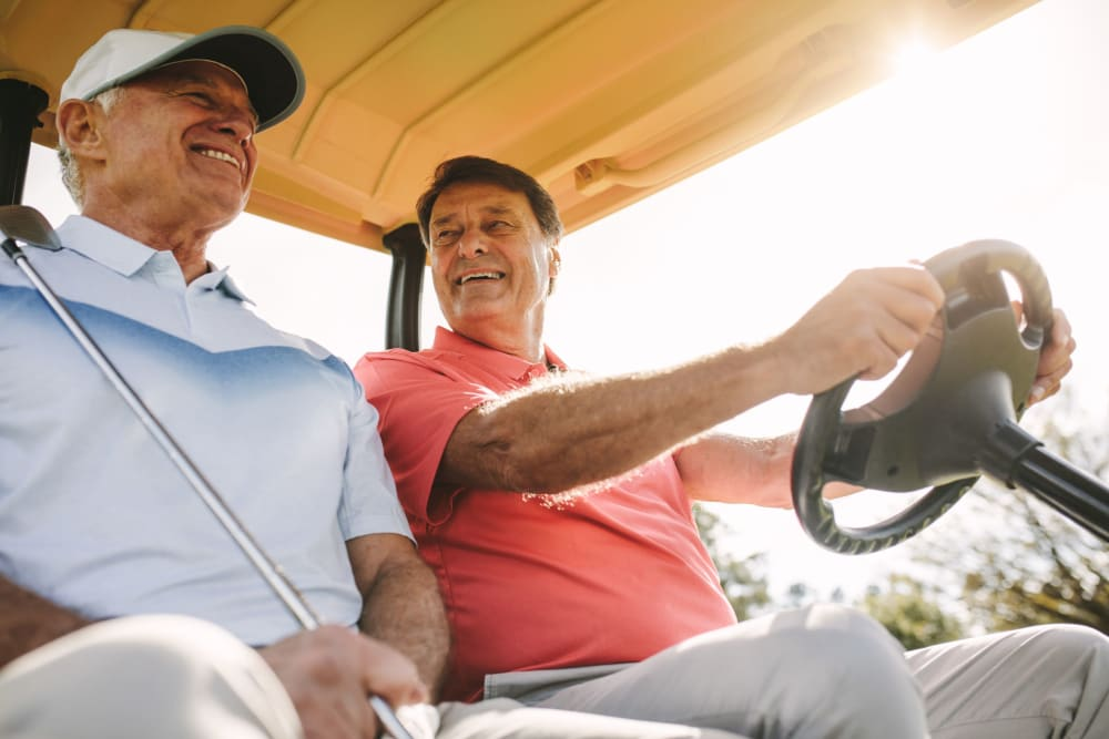 Residents driving a gold cart at a golf course near Castle Vista Senior Duplex Community in Atwater, California