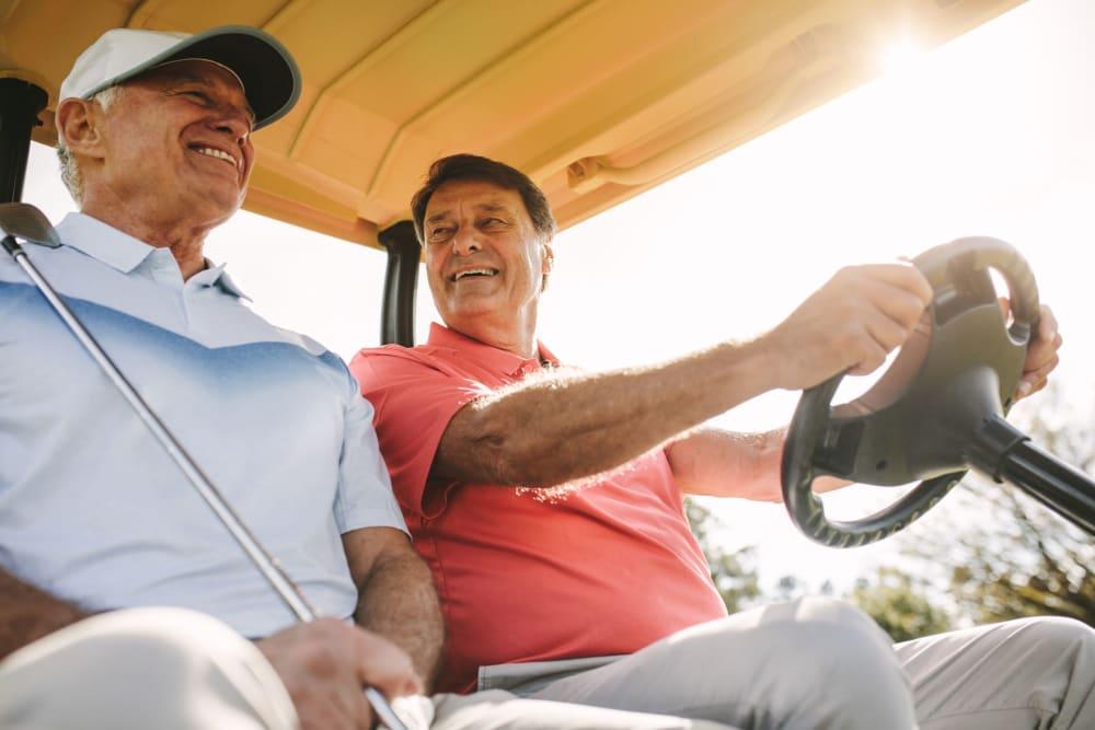 Residents driving a gold cart at a golf course near Leisure Manor Senior Living in Sacramento, California