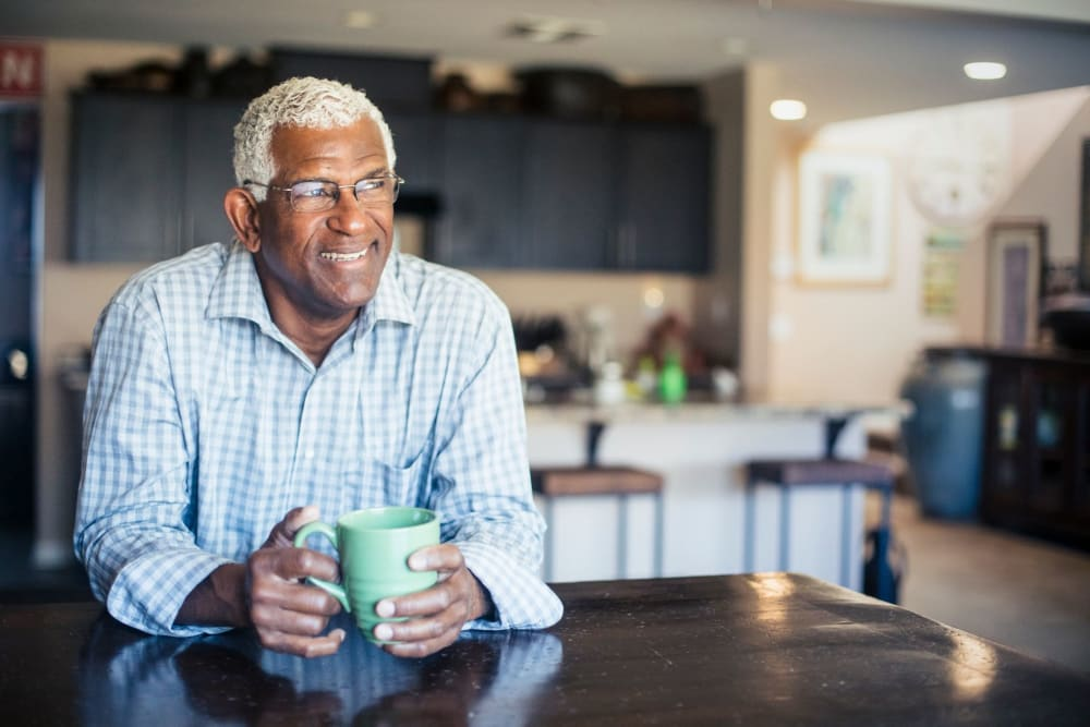Resident enjoying coffee in his living room at Hilltop Commons Senior Living in Grass Valley, California