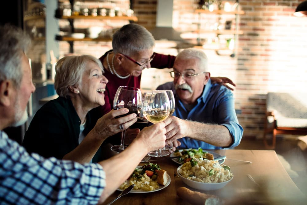 Friends sharing dinner and drinks at Hilltop Commons Senior Living in Grass Valley, California