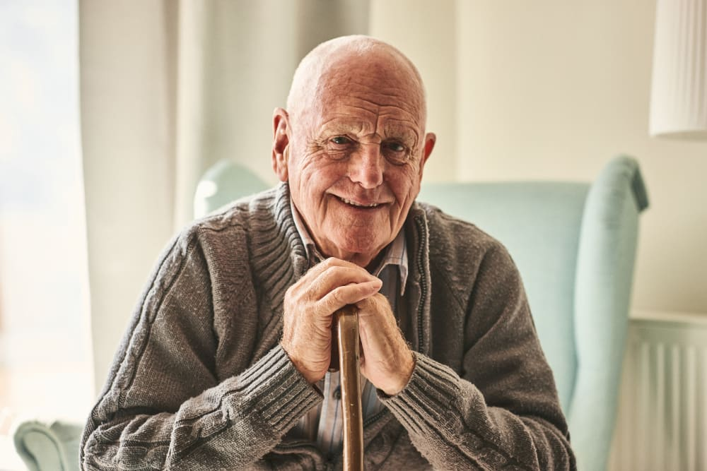 Resident smiling with a cane at Harmony at Enterprise in Bowie, Maryland