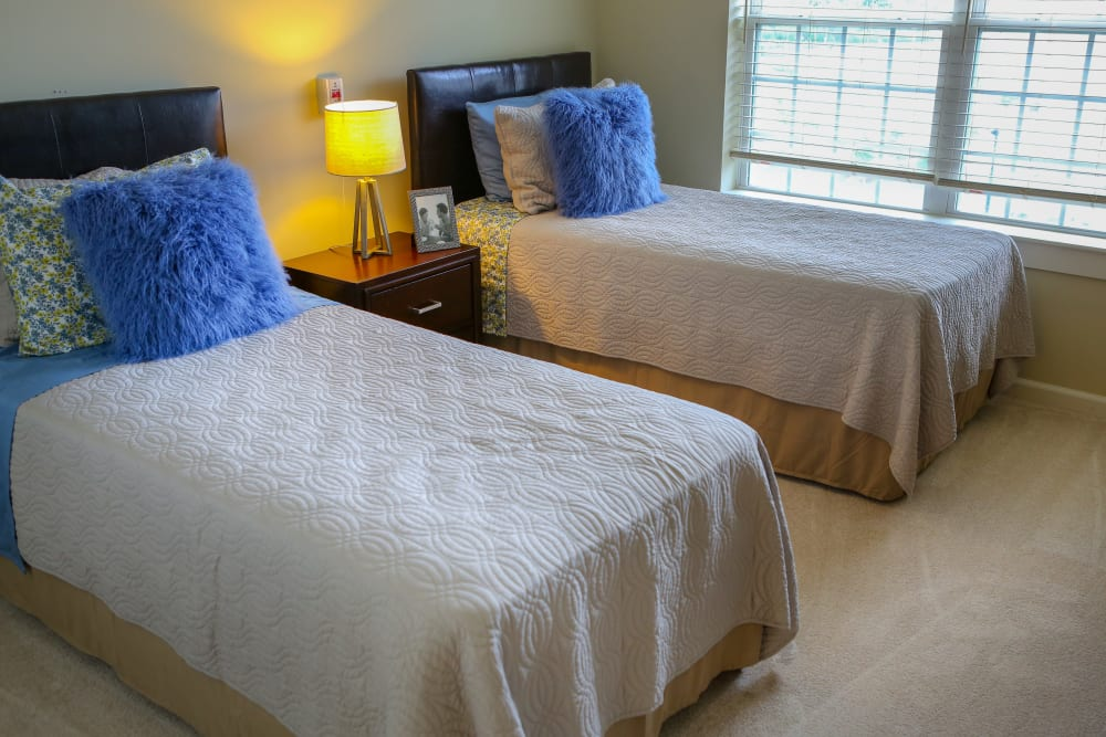 Twin beds in a bedroom at Harmony at Tucker Station in Louisville, Kentucky