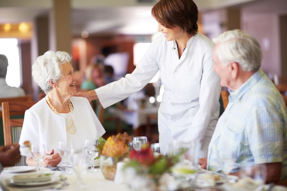 Chef laughing with seniors during meal service