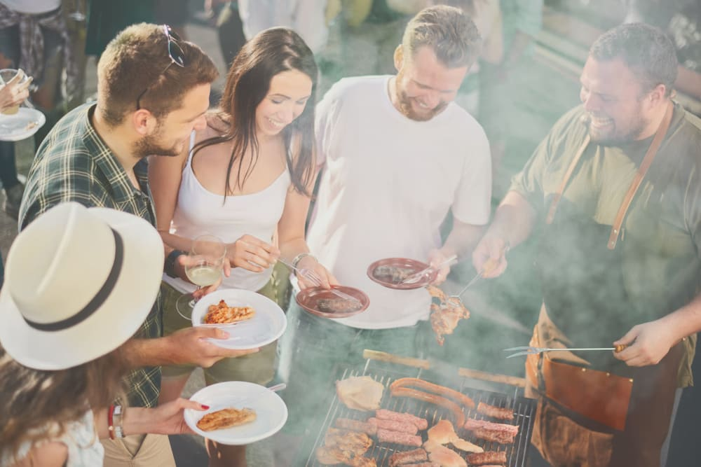 Resident having friends over in his private backyard for a barbecue at TerraLane at Canyon Trails in Goodyear, Arizona