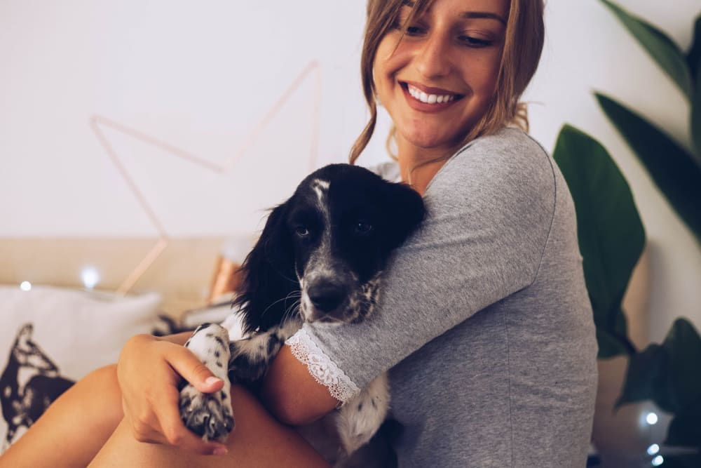 Resident and her dog relaxing in their home at TerraLane at South Mountain in Phoenix, Arizona