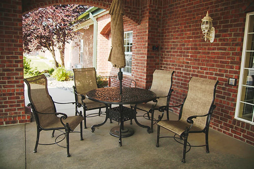 A covered patio with table and umbrella at Absaroka Senior Living in Cody, Wyoming